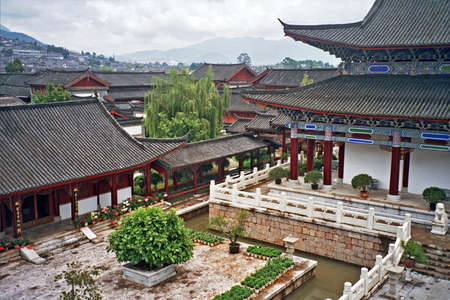 chinese courtyard: vintage style photo of fragments of ancient mu palace in lijiang, china with richly decorated large halls and beautiful courtyards and bridges