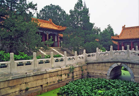 vintage style photo of chinese garden pavilions seen across the pond and decorated marble bridges in summer palace, Beijing, China Redakční