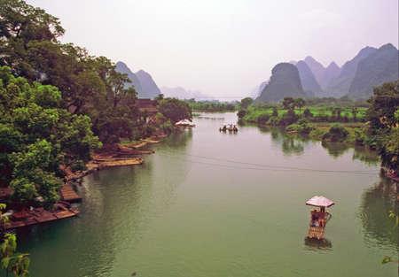 ビンテージ スタイルの一般的な中国の風景写真。前景の川、背景古代の村と山の中。場所 - Yanhsguo。 写真素材