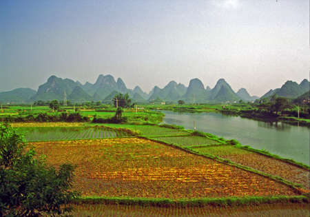 vintage style photo of  generic chinese landscape near yangshuo - river, rice fields and fantastically shaped mountains Reklamní fotografie