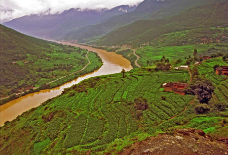 vintage style photo of aerial view of traditional village in china with old cottages and terraced fields and yellow river in background, leaping tiger gorge, yunnan, stylized and filtered to look like an oil painting