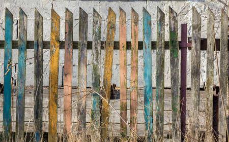 さまざまな色の板から成る古い崩壊しつつある木柵のフラグメント 写真素材