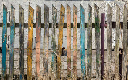 Fragment of an old crumbling wooden fence composed of planks of different colors