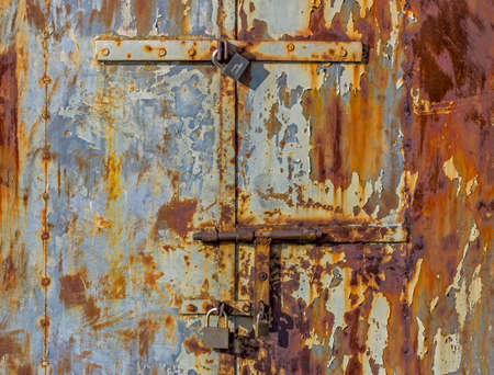 corroded bolts and padlocks on the door of a metal hut Reklamní fotografie