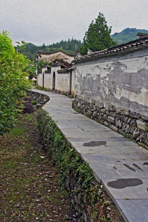 Stone pathway around the walls of xidi ancient village in Anhui province, China, vertical, stylized and filtered to resemble an oil painting