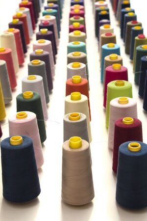 Many colorful yarns lined up in rows