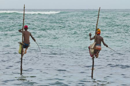 2 fishermen on sticks in the middle of the sea Stock Photo