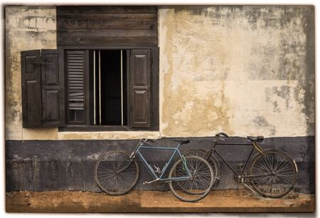 2 old bicycles lean on wall with an open window photo