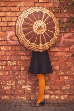 Fashionable woman hides behind an umbrella on brown wall