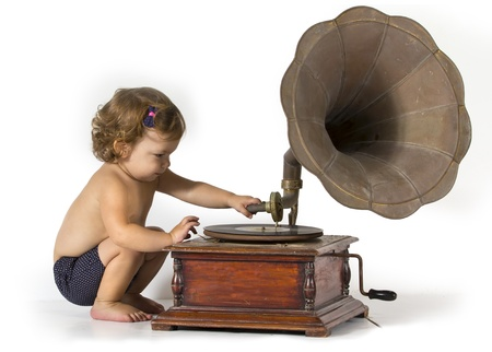 Baby girl sits and plays with an old gramophone Stock Photo