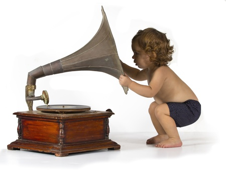 Baby girl get curious by an old gramophone photo