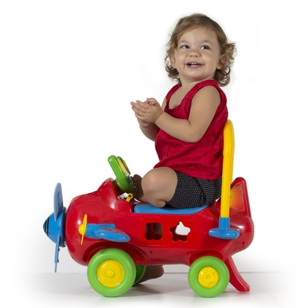 Happy baby girl sits on a red airplane toy and clapping hands