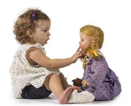 Baby girl gets fascinated by a vintage doll and play with her