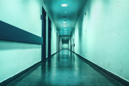 Long empty corridor washed in bluish depressive light good as depressive photography location Stock Photo