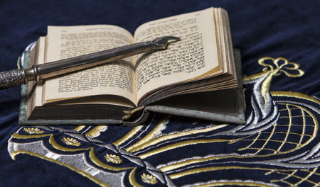hebrew alphabet: Open bible book in Hebrew with silver pointing hand stick on dark fabric with crown on it Stock Photo