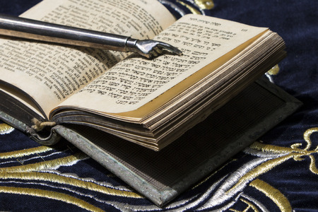 Open bible book in Hebrew with silver pointing hand stick on dark fabric with crown on it photo