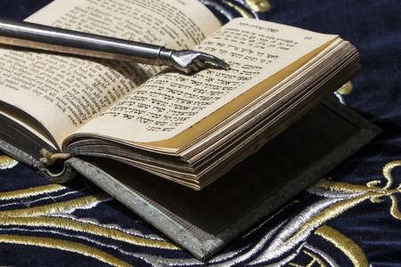 bible ouverte: Ouvert bible en hébreu avec pointage de bâton d'argent de la main sur le tissu sombre avec la couronne sur elle