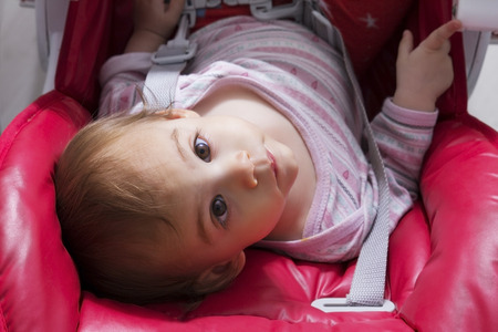 baby on chair: Baby sitting in red baby chair and looking up - Unusual viewpoint