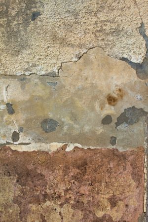 Layers of peeling plaster and paint on rough wall texture background