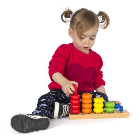 jardin de ni�os: Beb� que juega con el juguete de los anillos aislados en fondo blanco. Juego de buenas pr�cticas durante dos a�os de edad los beb�s
