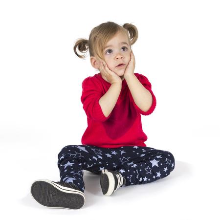 jardin de infantes: Beb� que se sienta y hacer un gesto con las manos en la cara aisladas sobre fondo blanco Foto de archivo