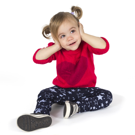 Baby girl sitting and covers her ears with the hands Stock Photo
