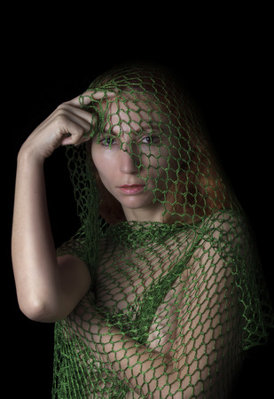 woman posing caught in the net and thinking on black background Stock Photo
