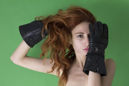 Woman covers her face with one hand with black glove on green background