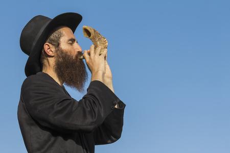 Orthodox Jewish man blast in Shofar at Rosh Hashana holiday on blue sky background Stock Photo