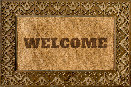 Rug for entrance with Welcome caption and beautiful ethnic ornaments on it in brown shades Stock Photo