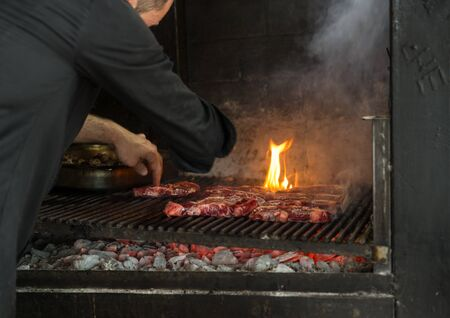 meat grill: Man puts pieces of fresh meat on the grill in a large oven with flame