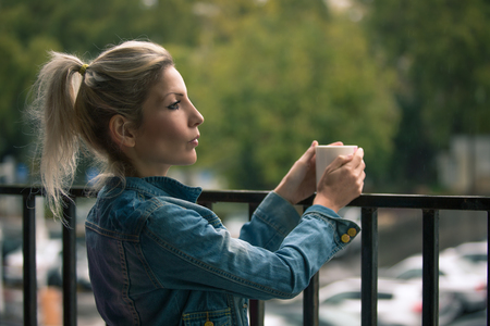 Profile of a blonde woman standing on the porch, holding a cup of coffee and looking out