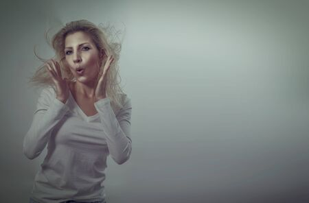 Surprised beautiful blonde woman show her emotions with hair flying on a gray background with retro effect
