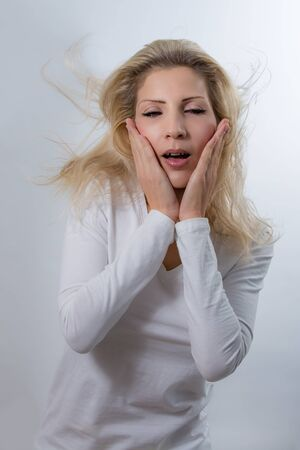 Surprised beautiful blonde woman show her emotions with hair flying on a gray background Stock Photo