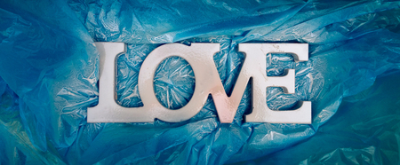 LOVE typography - Just painted white sign in honor of Valentines Day on a blue background