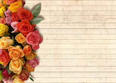 A floral background with a bouquet of flowers on the side and an empty pale wood panel for copy space Stock Photo