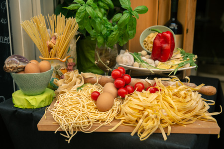 Stylish decoration of basic ingredients of Italian food - pasta, spaghetti, eggs, tomatoes and garlic Stock Photo