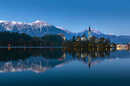 Scenic view of lake Bled at winter night with castle rock and St Martin church under beautiful blue sky reflected in lake water