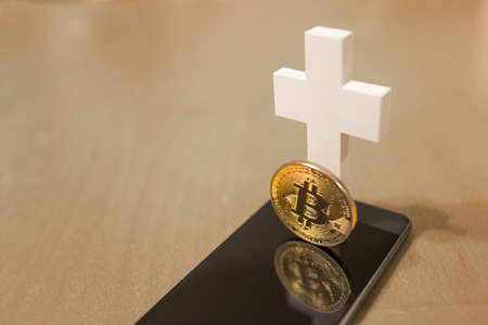 Dead Bitcoin concept with white cross and smartphone as grave