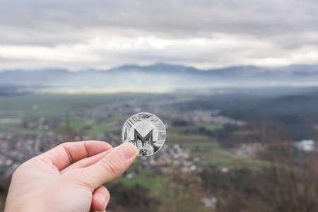 Monero silver coin, Hand hold Monero above the city