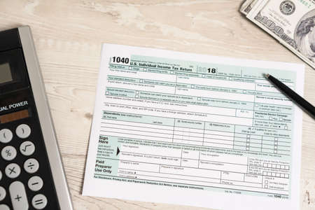 US tax form 1040 with pen, calculator and dollar bills. tax form law document usa white business concept