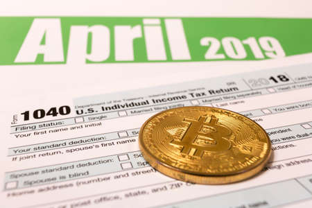 Bitcoin with 1040 income tax form for 2018 showing tax day for filing on April 15