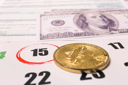 Bitcoin and 2019 calendar with 1040 income tax form for 2018 showing tax day for filing on April 15 Stock Photo