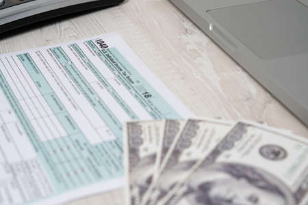 US tax form 1040 with dollar bills. tax form in focus. tax form law document usa white business concept