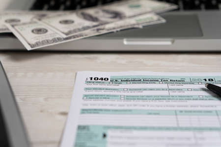 US tax form 1040 with pen and dollar bills. tax form law document usa white business concept