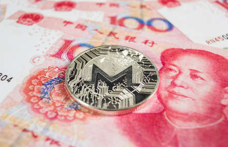 Crypto currency concept - A Monero coin with Chinece currency RMB, Renminbi, yuan Stock Photo