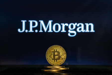 Bitcoin on a stack of coins with JPMorgan logo on a laptop screen. Cryptocurrency and blockchain adoption getting mainstream. Slovenia - 02 24 2019 Editorial