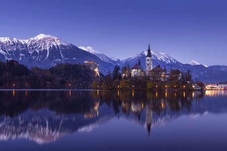 Schilderachtig uitzicht op het meer van Bled in de winternacht met kasteelrots en St. Martin-kerk onder een prachtige sterrenhemel die wordt weerspiegeld in het water van het meer Stockfoto