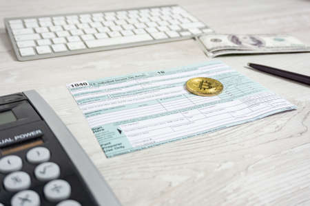 The pen, bitcoins and calculator on the tax form 1040 U.S. Individual Income Tax Return. The time to pay taxes