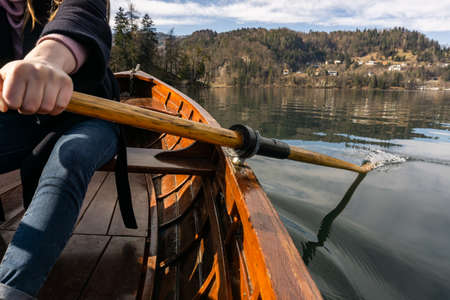Young woman using paddle on a wooden boat - Lake Bled Slovenia rowing on wooden boats Banque d'images